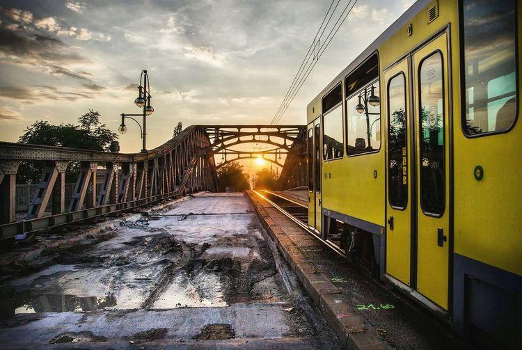 Train on bridge against sky during sunset