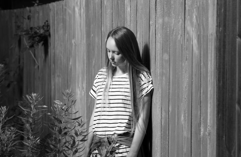 Sad teenage girl looking at plants while standing by wooden fence at backyard