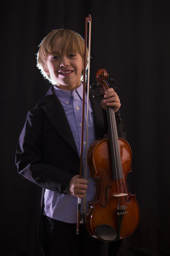 Boy holding violin while standing against black background