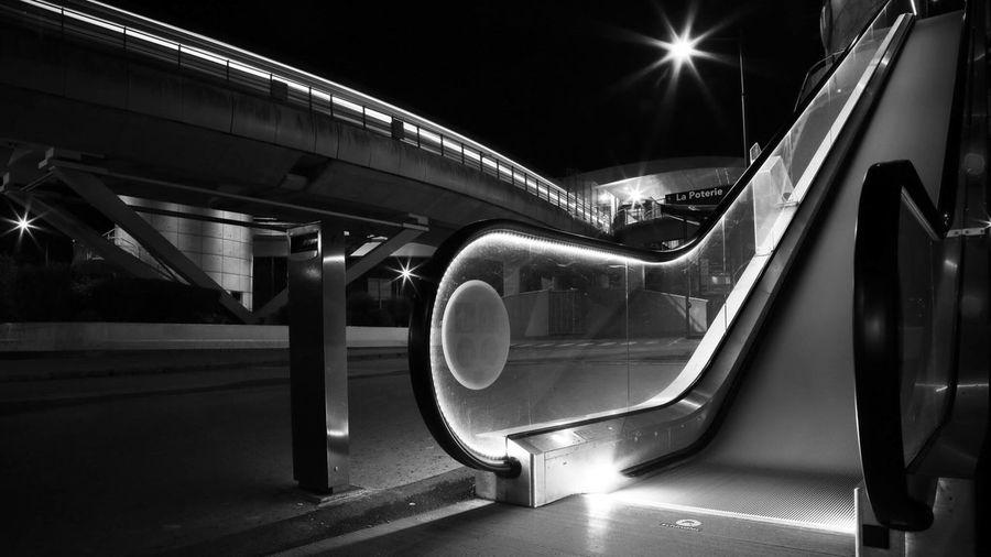 Illuminated Escalator By Bridge In City At Night
