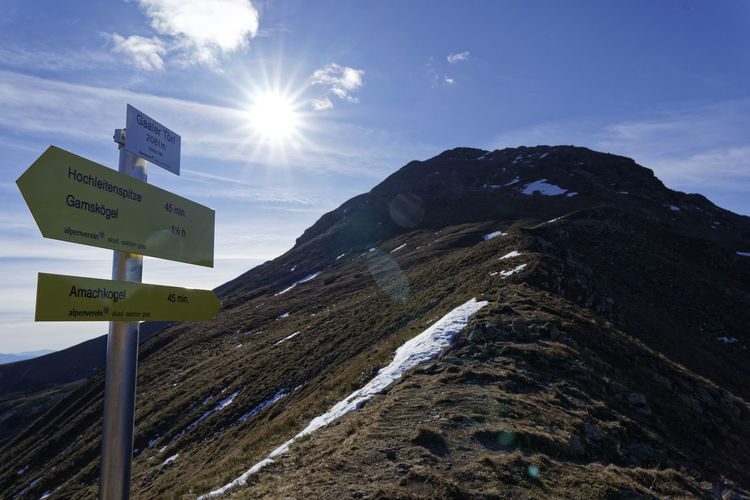 Information sign on mountain against sky