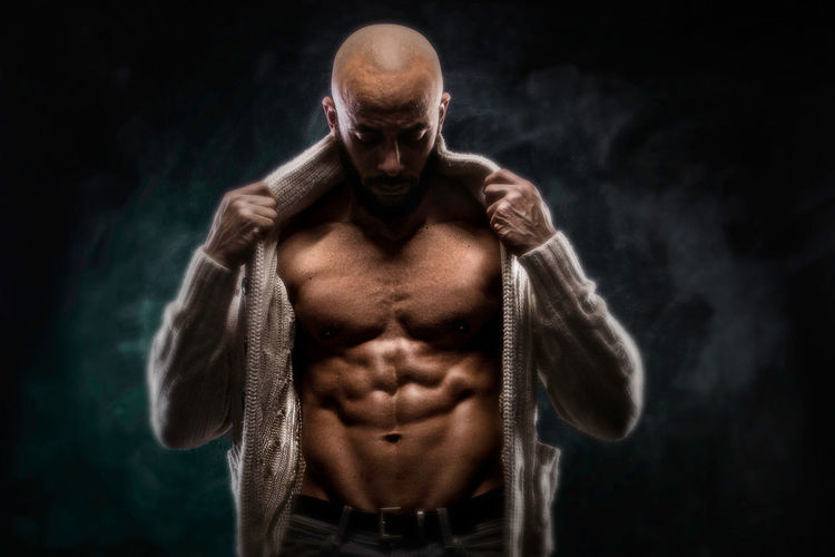 Bald Muscular Man Standing Against Black Background