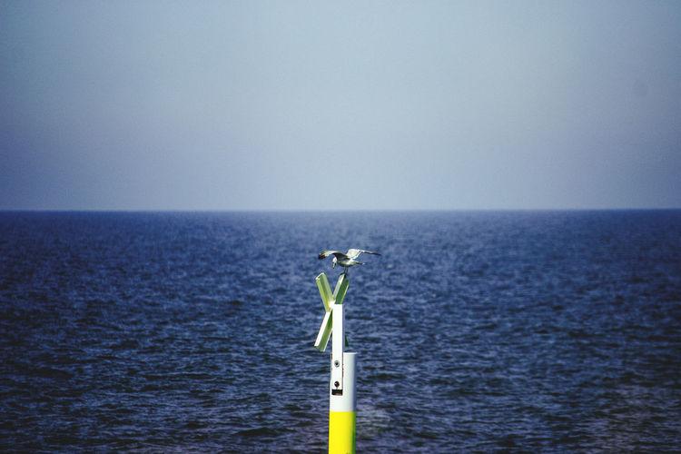 Cross on sea against clear sky