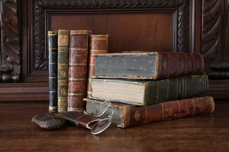 old books piled on a wooden table Antique Books Bookshelf Bookshelfs Horizontal Learning Library Read Reading Reading Glasses Book Close Up Collection Cover Culture Indoors  No People Old Piled Reading A Book Traditional Wood - Material