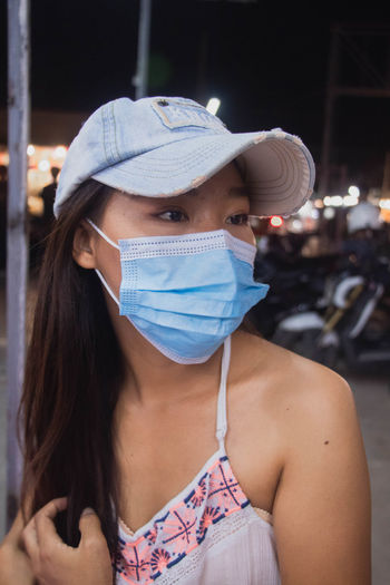 Close-up of young woman wearing flu mask and cap looking away standing outdoors