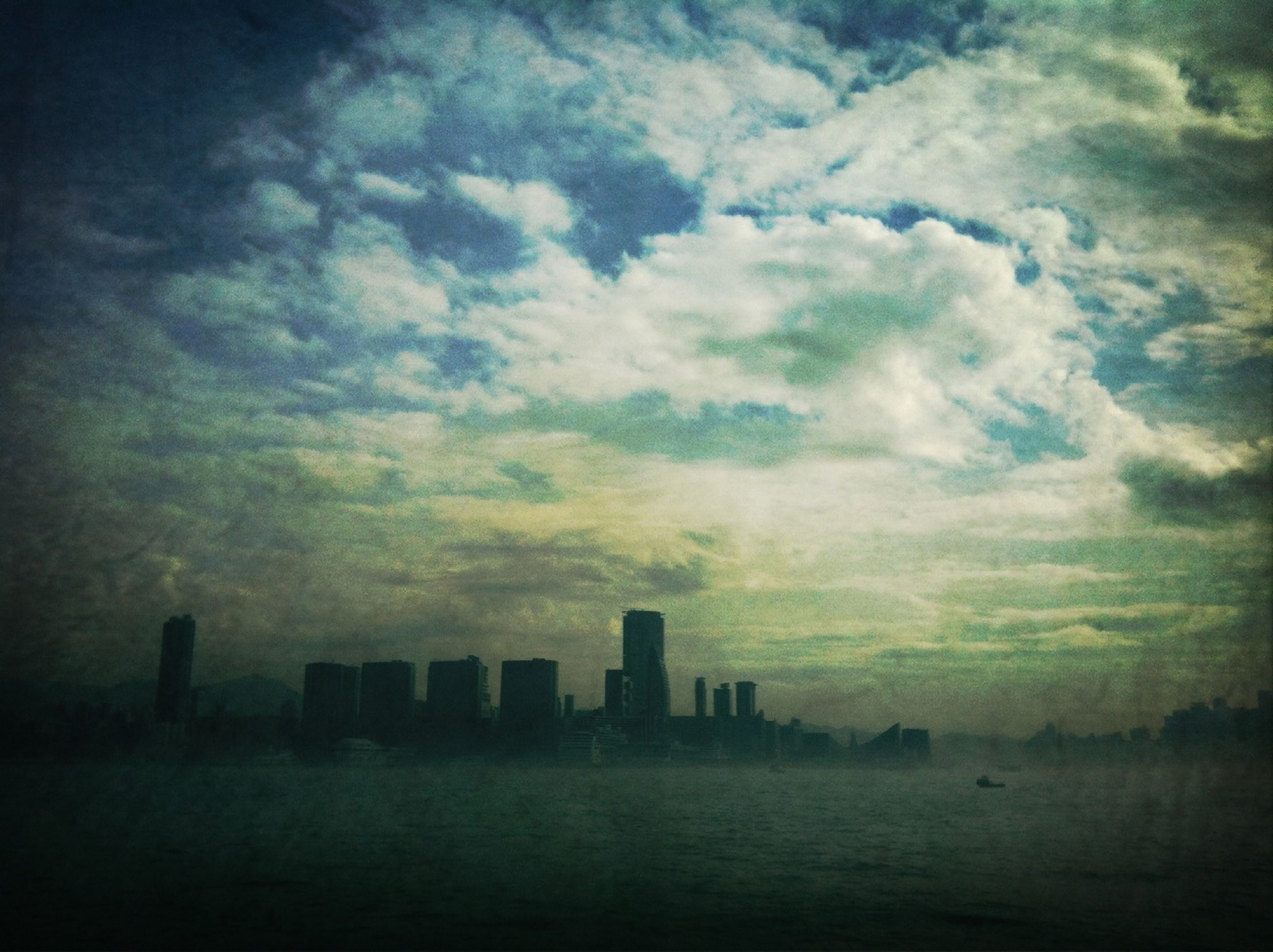 sky, waterfront, building exterior, cloud - sky, architecture, city, water, sea, built structure, skyscraper, cloudy, cityscape, urban skyline, sunset, cloud, scenics, weather, dusk, nature, tranquility