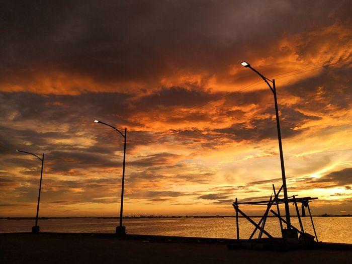 Silhouette street lights by sea against orange sky