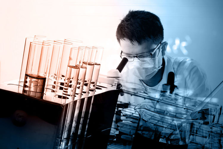 Close-Up Of Doctor Looking In Microscope In Laboratory