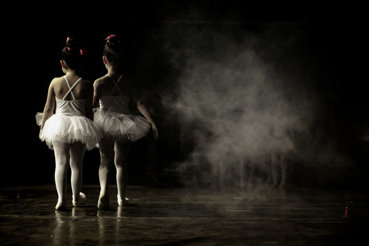 Rear View Of Ballet Dancers Walking On Stage