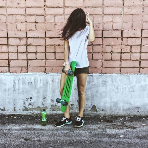Brick Wall Wall - Building Feature Standing Full Length Casual Clothing Young Women Sidewalk Long Hair Lifestyles Young Adult Femininity Person Outdoors Day Green Color