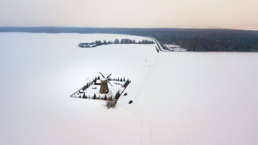 Traditional windmill on snow covered landscape against sky