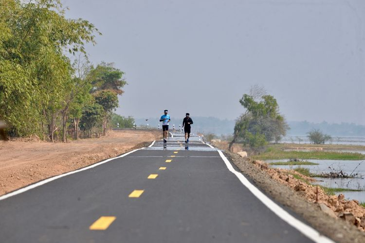 Full length of people jogging on road against sky