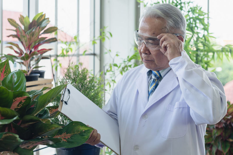Man wearing mask holding while standing against plants