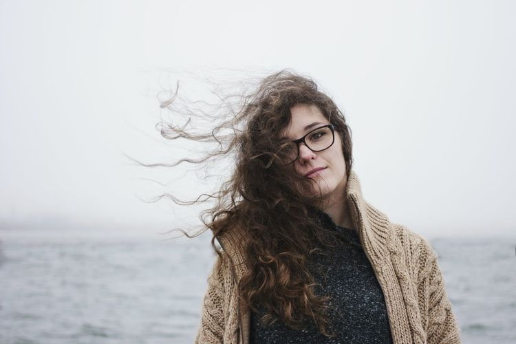 Portrait of beautiful young woman by sea