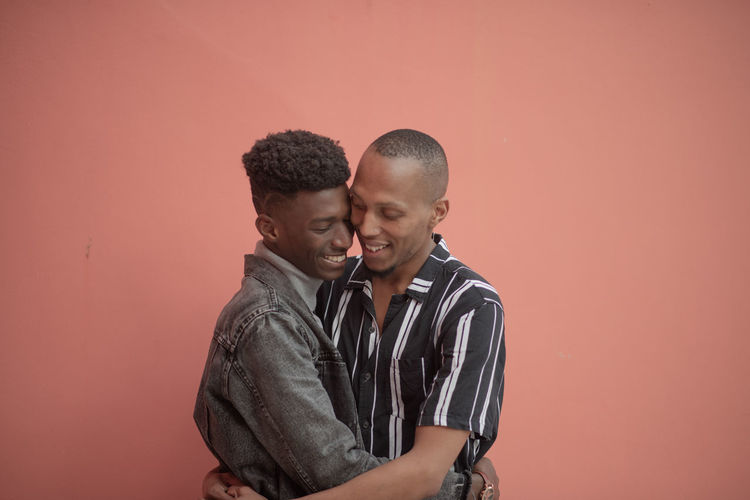 Gay couple embracing while standing against wall
