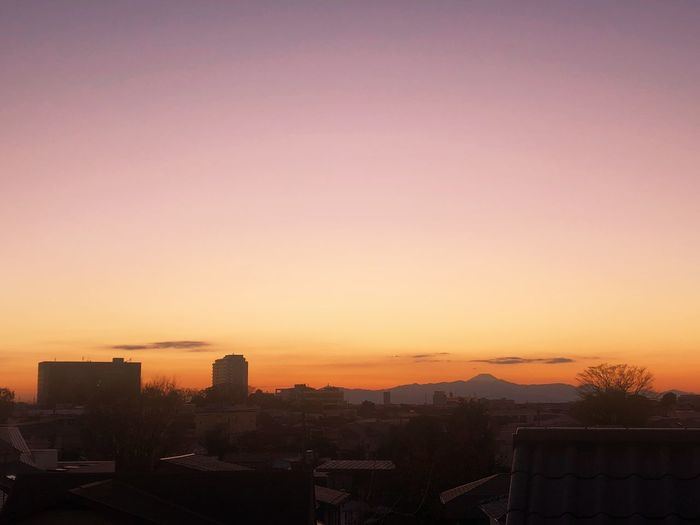 High angle view of silhouette buildings against sky during sunset
