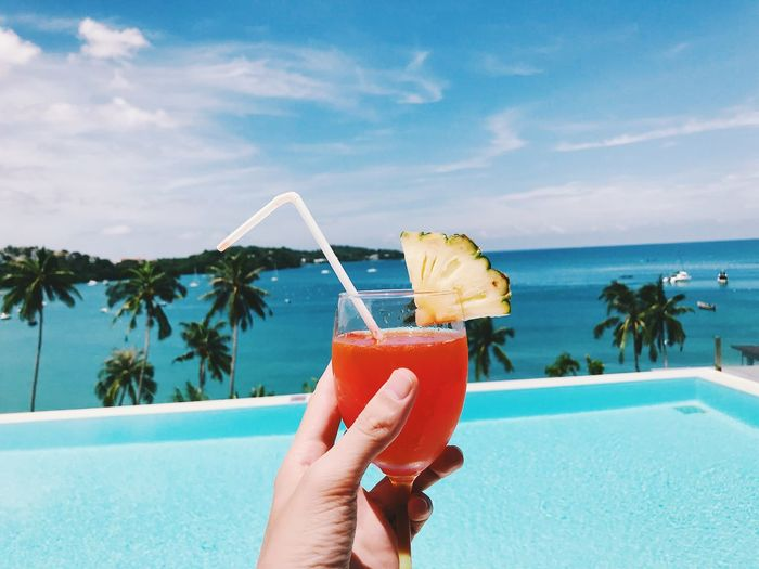 Cropped hand holding drink by infinity pool with sea in background