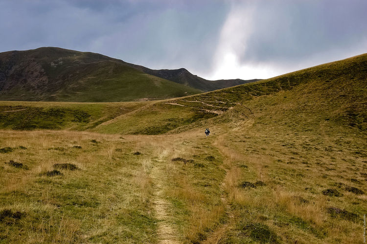 Avant l'orage, dans les Pyrénées Arid Climate Before The Storm Countryside Dark Sky Day Field Geology Grass Hill Landscape Majestic Mountain Mountain Range Nature Non-urban Scene Outdoors Path Physical Geography Pyrenees Remote Solitude Walkers