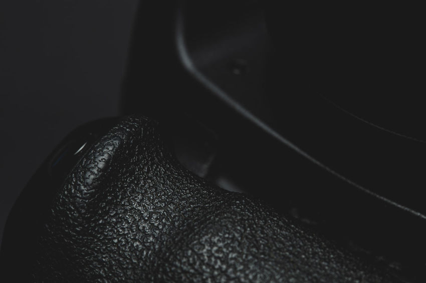 close up view of a DSLR camera grip in dark atmosphere Close-up Indoors  Black Color Studio Shot Winter Black Background Still Life Luxury Grip Camera Photography Photographer Equipment Shutter Videography Gear Ergonomics Low Key Videographer Alloy Magnesium DSLR Object