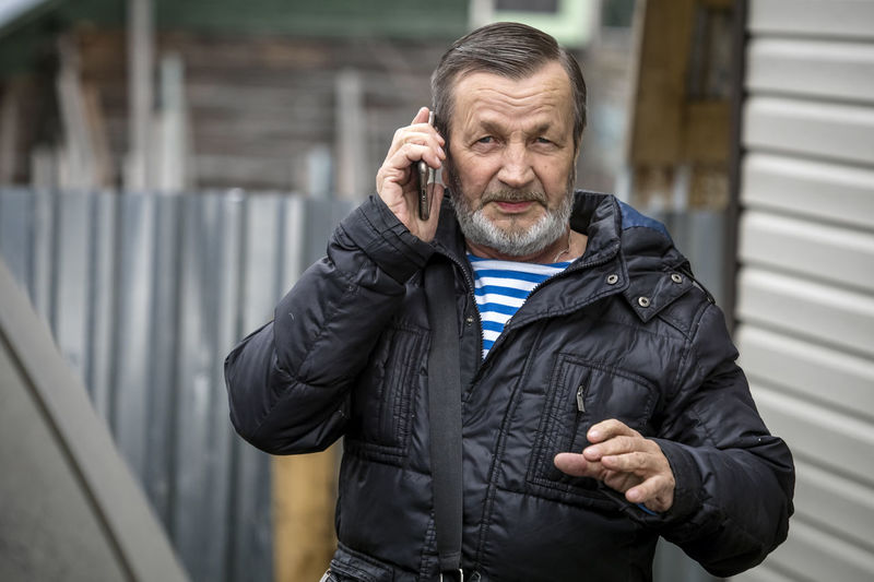Mid adult man using smart phone outdoors