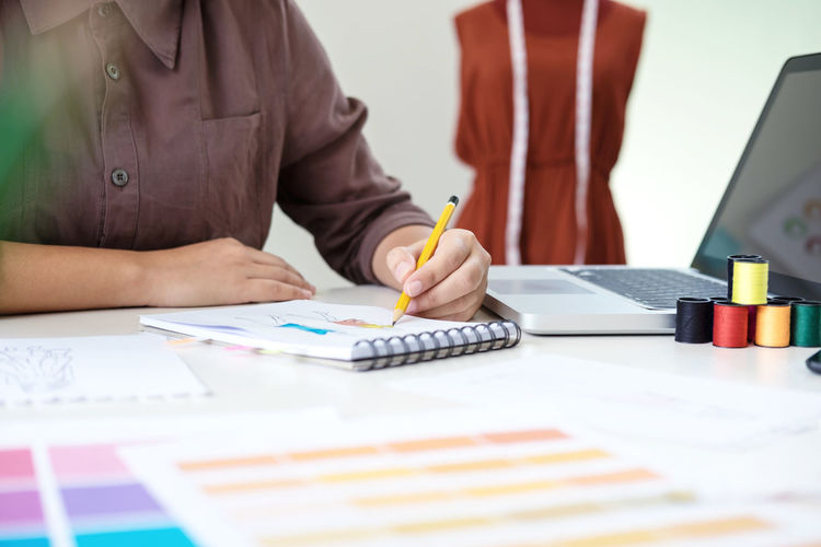 Midsection of female fashion designer drawing on book at desk