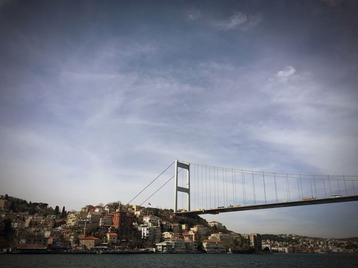 Bridge over sea by city against sky
