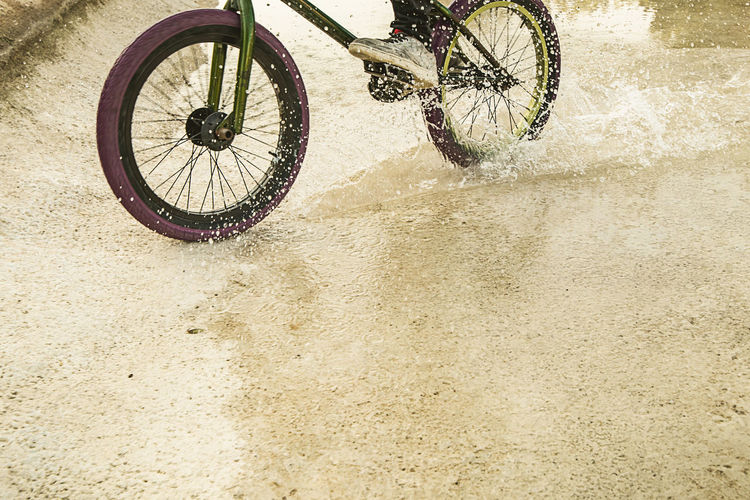 Bicycle parked on wet land