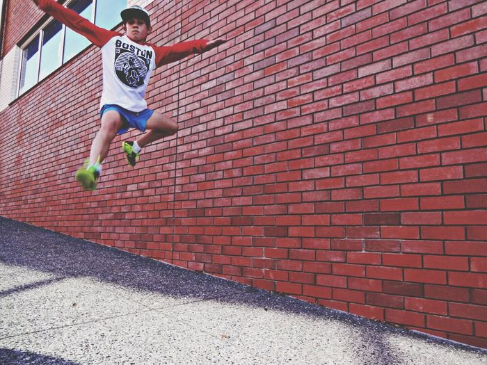 Low angle view of boy jumping against brick wall