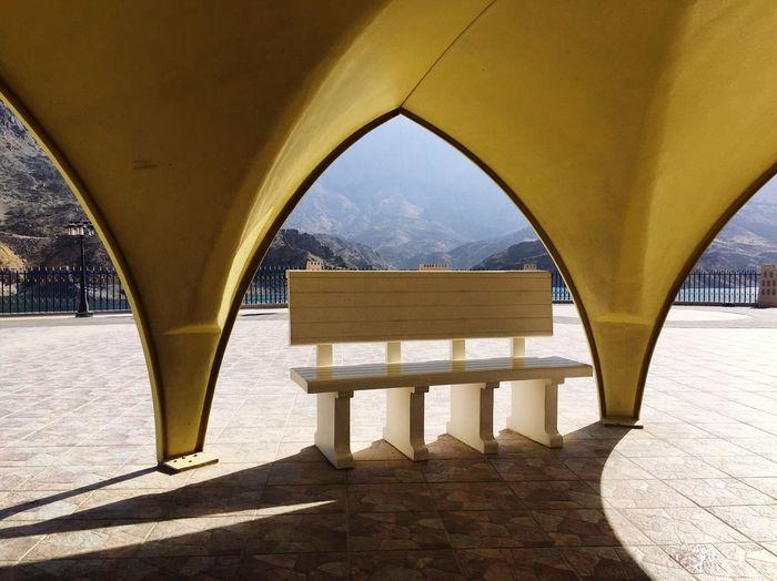Empty bench below arch on footpath