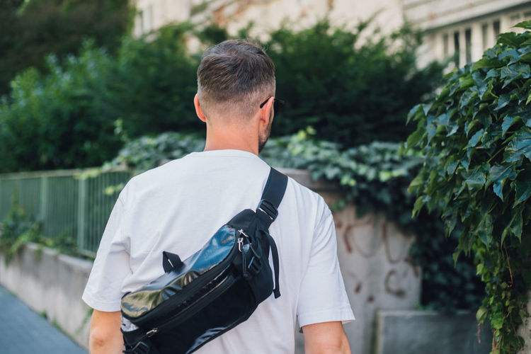 Rear view of man wearing backpack standing outdoors