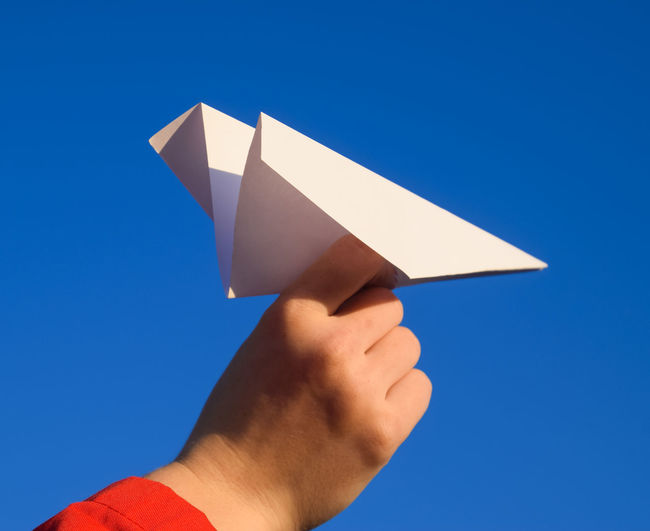 Close-up of hand holding paper against blue sky