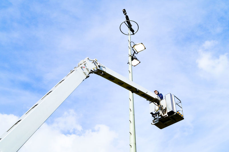 Low angle view of man standing in cherry picker against sky