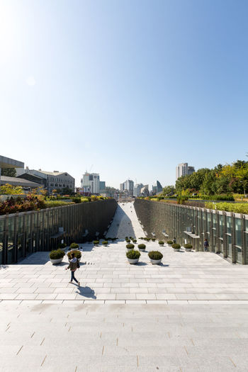 Campus of EWHA - Woman's University of Seoul, south Korea. Architket: Dominique Perrault Architecture Perrault Seoul Seoul, Korea Adult Architecture Building Exterior Built Structure City Cityscape Clear Sky Day Ewha Ewha Womans University Full Length Leisure Activity Lifestyles Men One Person Outdoors People Real People Sky Sunlight Walking Water Women