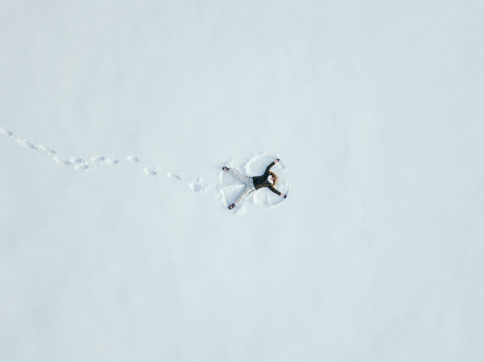High Angle View Of Young Woman Making Snow Angel