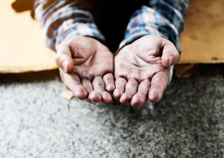 Cropped hands of mature man begging on floor