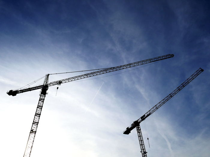 Low angle view of cranes and construction site against sky