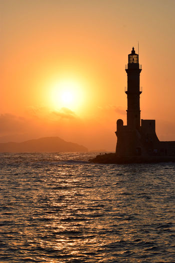 Watching the sunset from the port of Chania Chania Architecture Beauty In Nature Built Structure Crete Greece Guidance Lighthouse Mountain Nature No People Orange Color Outdoors Safety Scenics - Nature Sea Security Sky Sun Sunset Tower Travel Destinations Water Waterfront