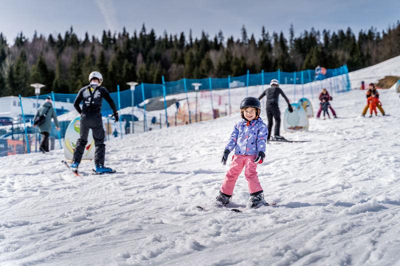 Full length of children on snow covered mountain