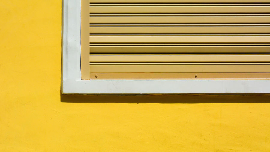 Close-up of window on yellow wall