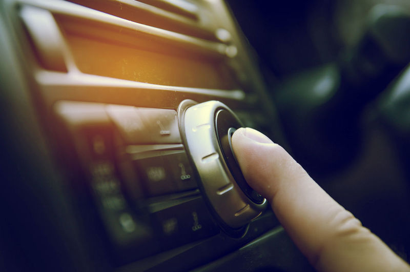 Cropped Image Of Human Finger Touching Music System In Car
