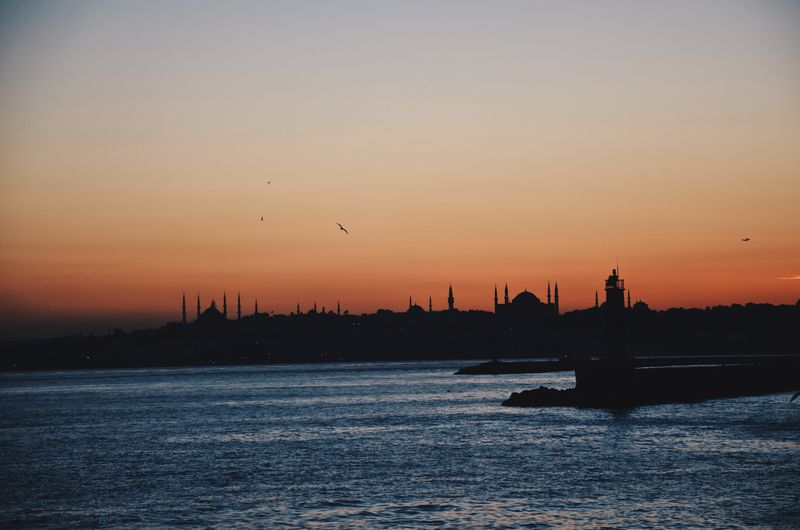 Silhouette Mosque And Lake Against Sky During Sunset In City