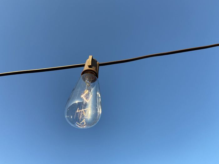 Low angle view of light bulb against blue sky