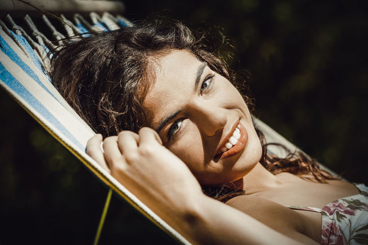 Close-Up Portrait Of Smiling Young Woman Lying On Hammock