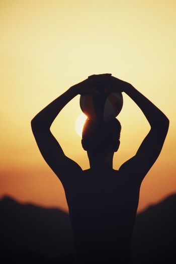Silhouette man with volleyball against sky during sunset