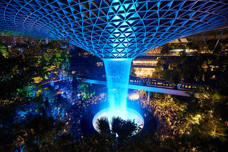 Jewel Changi Airport Water Vortex Fountain Blue Architecture Illuminated Built Structure Nature Tree No People Plant Night Building Exterior Outdoors City Bridge Motion Bridge - Man Made Structure Lighting Equipment Glowing