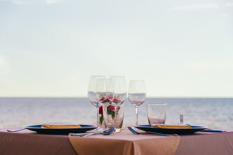 Close-Up Of Wine Glasses On Table At Restaurant Against Sea