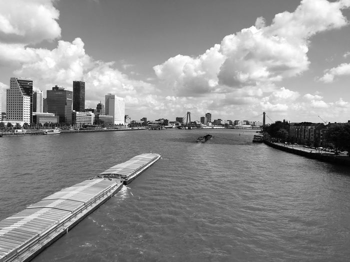 View Of City At Waterfront Against Cloudy Sky
