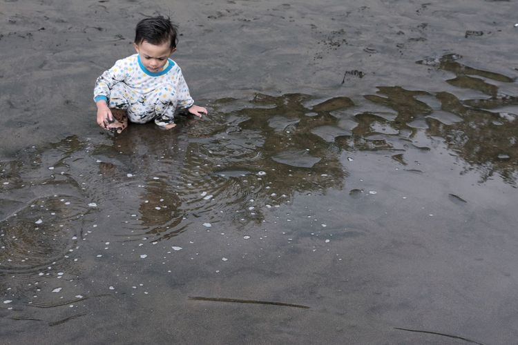 High Angle View Of Boy Sitting At Beach