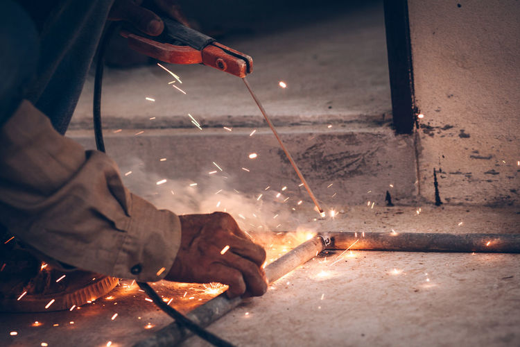 Cropped image of worker welding rods in factory