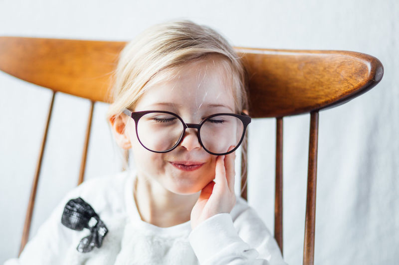 Close-up of cute girl wearing big eyeglasses while sitting on chair at home